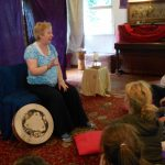 Photo of Betty sitting in her storytelling chair with a drum at her feet and a captive audience